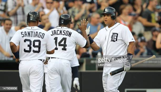 Miguel Cabrera of the Detroit Tigers congratulates teammates Austin Jackson and Ramon Santiago after they scored on a triple to deep center field by...