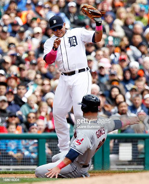 Miguel Cabrera of the Detroit Tigers has to leap for the ball as Yan Gomes of the Cleveland Indians slides safe into third base in the third inning...