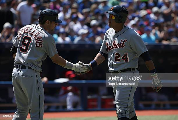 Miguel Cabrera of the Detroit Tigers is congratulated by Nick Castellanos after scoring a run in the third inning during MLB game action against the...