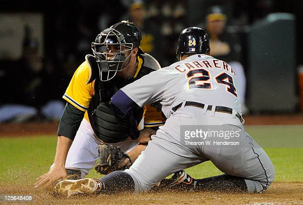 Miguel Cabrera of the Detroit Tigers is tagged out at the plate by Landon Powell of the Oakland Athletics in the fourth inning during an MLB baseball...