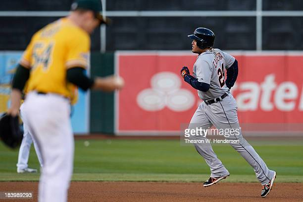 Miguel Cabrera of the Detroit Tigers rounds the bases on his fourth inning tworun home run as Sonny Gray of the Oakland Athletics reacts during Game...