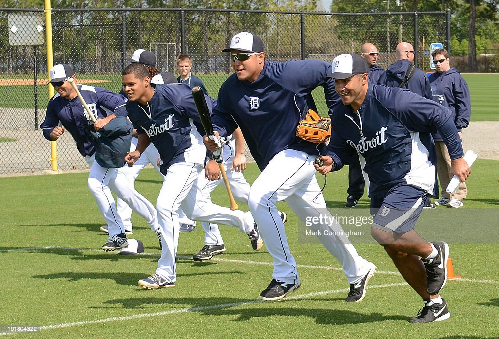 Miguel Cabrera #24 of the Detroit Tigers runs wind sprints with strength coach Javair Gillett (R) and teammates during Spring Training workouts at the TigerTown Facility on February 16, 2013 in Lakeland, Florida.