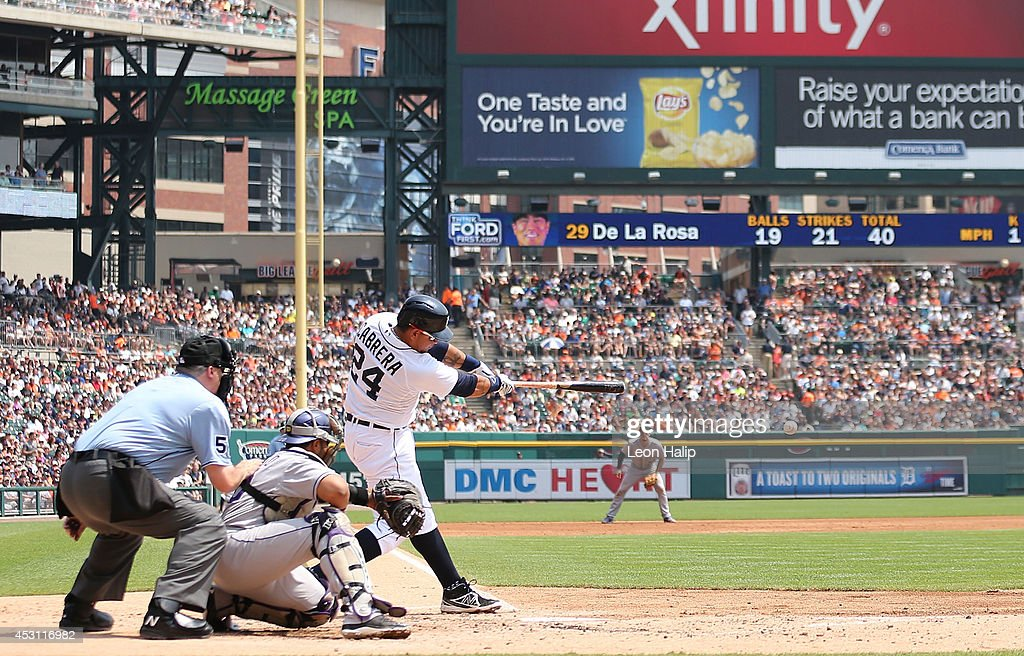 Miguel Cabrera #24 of the Detroit Tigers singles to center field scoring Rajai Davis #20 during the third inning of the game against the Colorado Rockies at Comerica Park on August 3, 2014 in Detroit, Michigan.