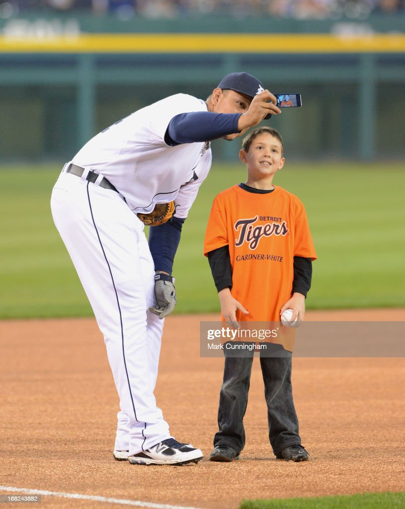 Miguel Cabrera #24 of the Detroit Tigers takes a photo of himself and a young fan with a cell phone prior to the game against the Atlanta Braves at Comerica Park on April 28, 2013 in Detroit, Michigan. The Tigers defeated the Braves 8-3.