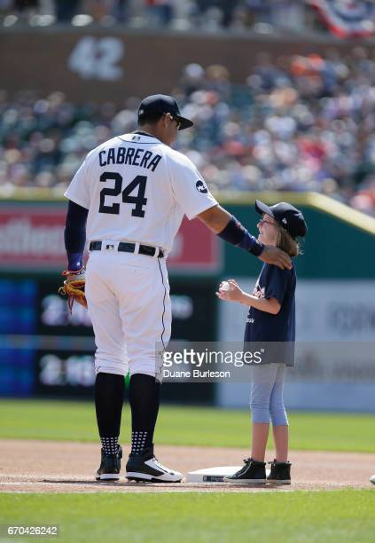 Miguel Cabrera of the Detroit Tigers talk with a young girl after giving her a baseball at first base before their game against the Boston Red Sox at...