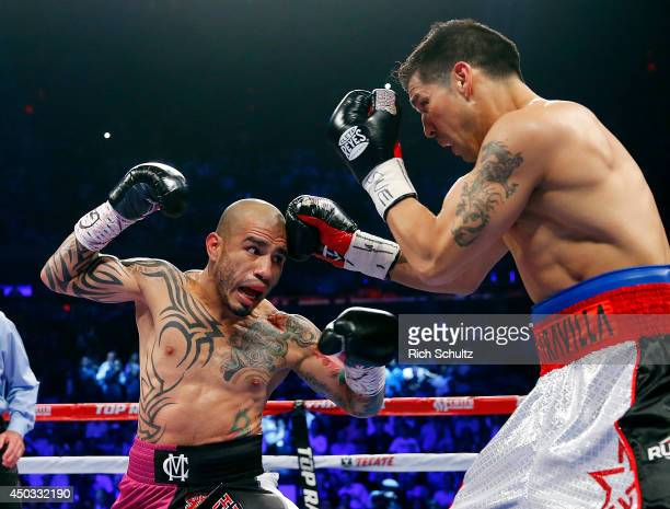 Miguel Cotto left of Puerto Rico takes a punch to the head by Sergio Martinez of Argentina during the first round as they battle for the WBC...