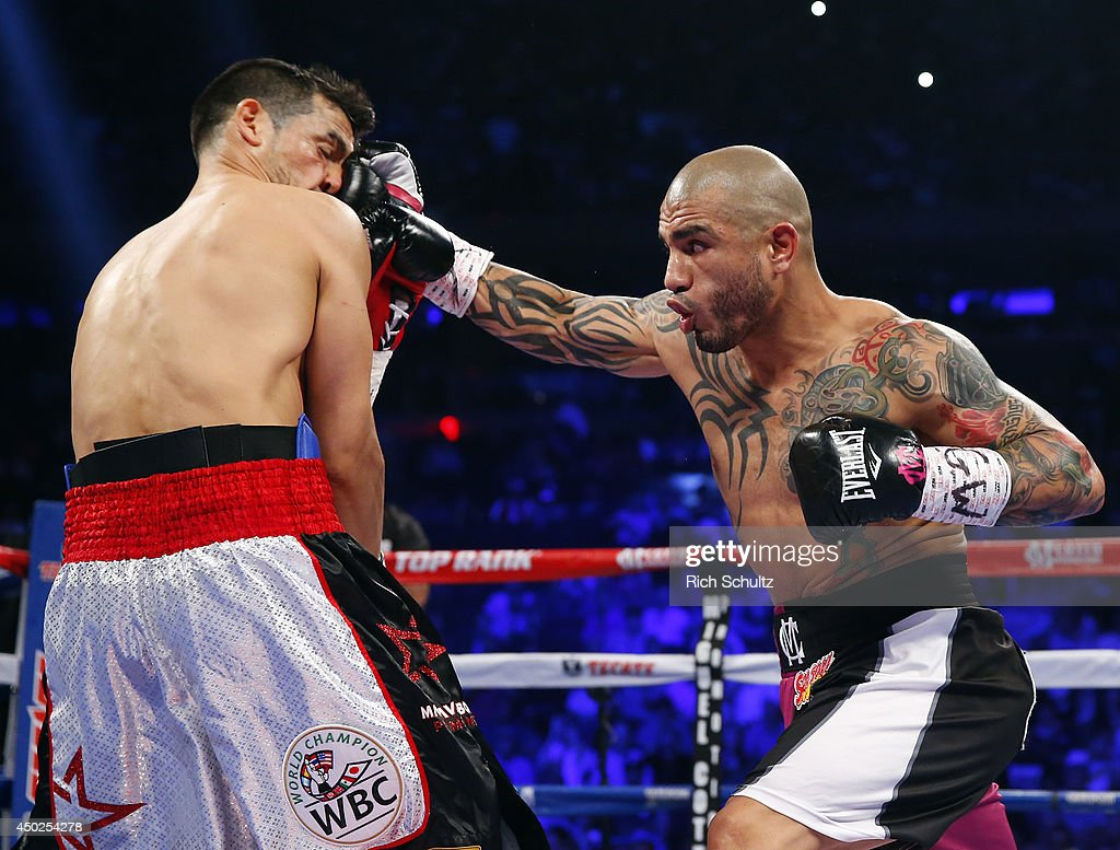 Miguel Cotto of Puerto Rico (R) lands a right punch to the face of Sergio Martinez of Argentina during the first round as they battle for the WBC Middleweight Championship on June 7, 2014 at Madison Square Garden in New York City. Cotto won by a TKO in the ninth round.