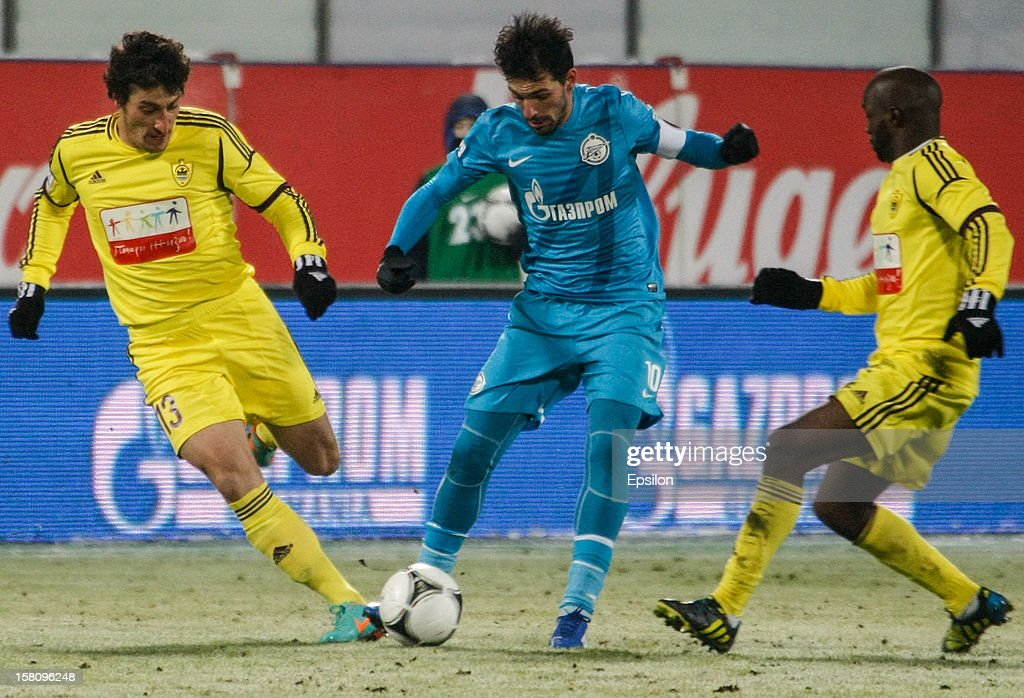 Miguel Danny of FC Zenit St. Petersburg passes the ball as Rasim Tagirbekov of FC Anzhi Makhachkala (L) and Lassana Diarra of FC Anzhi Makhachkala (R) defend during the Russian Football League Championship match between FC Zenit St. Petersburg and FC Anzhi Makhachkala at the Petrovsky Stadium on December 10, 2012 in St. Petersburg, Russia.