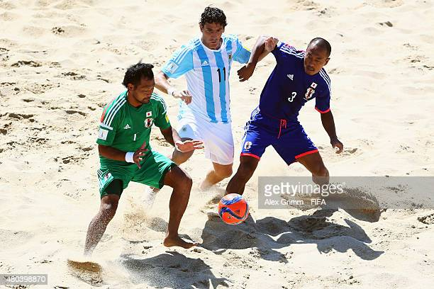 Miguel de Ezeyza of Argentina is challenged by goalkeeper Shingo Terukina and Hirofumi Oda of Japan during the FIFA Beach Soccer World Cup Portugal...