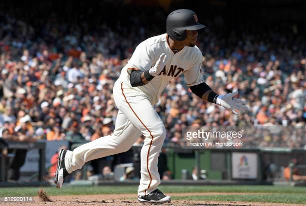 Miguel Gomez of the San Francisco Giants celebrates clapping his hands as he runs up the first base line with his first Major League career base hit...