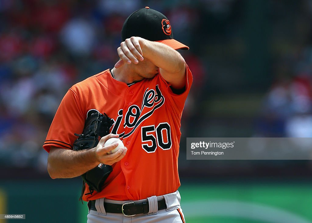 Miguel Gonzalez #50 of the Baltimore Orioles reacts after giving up a run against the Texas Rangers in the bottom of the first inning at Globe Life Park in Arlington on August 30, 2015 in Arlington, Texas.