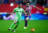 Miguel Guerrero of Real Sporting de Gijon duels for the ball with Mehdi Lacen of Getafe CF during the La Liga match between Real Sporting de Gijon...
