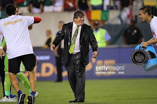 Miguel Herrera the head coach / manager of Mexico gets soaked with water by Paul Aguilar of Mexico during the celebrations after the 2015 CONCACAF...