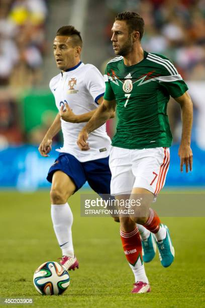Miguel Layun of Mexico runs with the ball as Joao Moutinho of Portugal chases him during the Internatinal friendly match between Mexico and Portugal...