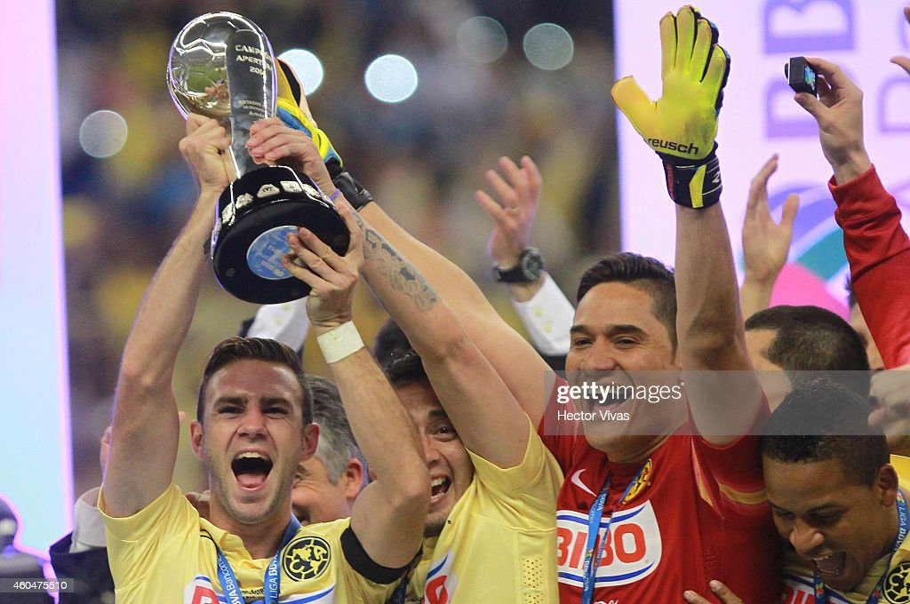 Miguel Layun, Rubens Sambueza and Moises Mu–noz of America raise the champions trophy after a Final second leg match between America and Tigres UANL as part of the Apertura 2014 Liga MX at Azteca Stadium on December 14, 2014 in Mexico City, Mexico.
