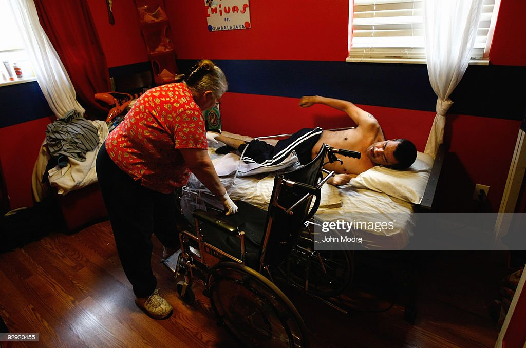Miguel Lopez (R), largely paralyzed from the chest down, turns himself in bed as personal care provider Mary Gordillo helps him into his wheelchair at his home on November 9, 2009 in Lakewood, Colorado. Lopez, a Mexican immigrant whose three children were born in the United States and are American citizens, broke his neck last summer while playing with his daughters on a backyard trampoline. Formerly a construction worker, Lopez had no health insurance when the accident occurred. He receives home health care visits from Dominican Sisters Home Health Agency, a non-profit that performs some 25,000 home visits each year in the Denver area. It provides free home nursing care to patients with chronic diseases, helps them to better manage their disabling illnesses and provides custodial services with the aim of keeping patients in their homes and out of more expensive nursing home care.