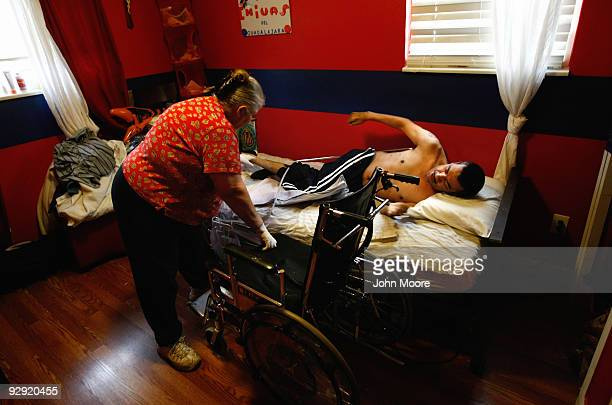 Miguel Lopez largely paralyzed from the chest down turns himself in bed as personal care provider Mary Gordillo helps him into his wheelchair at his...
