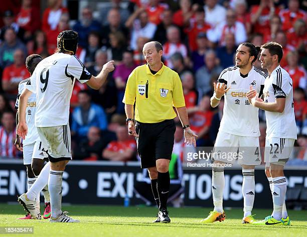 Miguel Michu Angel Rangel and Chico Flores of Swansea City protest to referee Mike Dean during the Barclays Premier League match between Southampton...