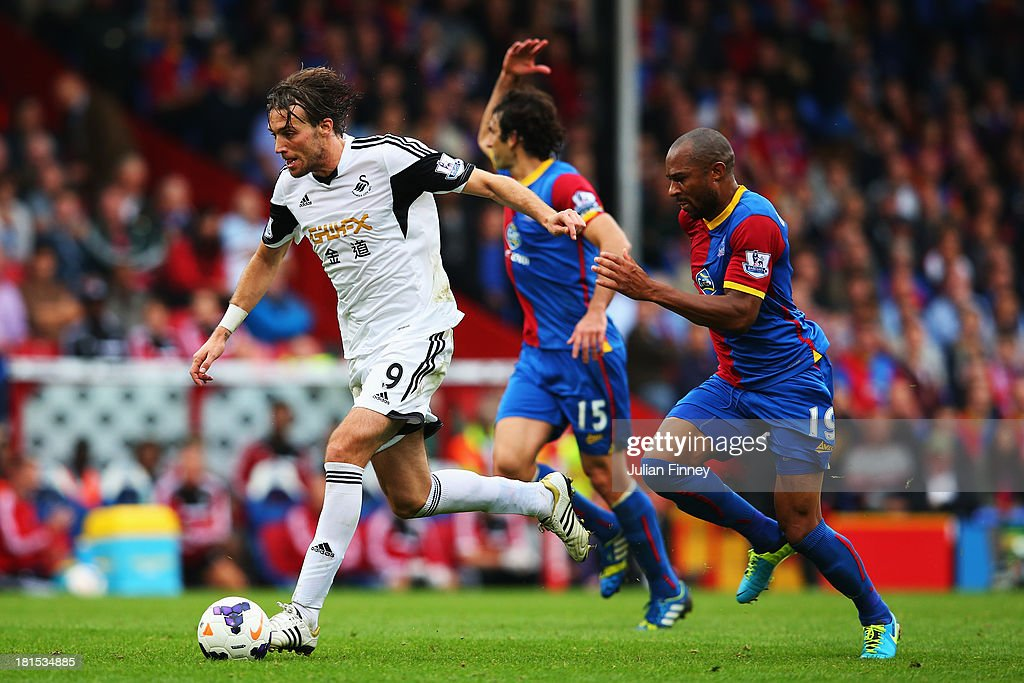 Miguel Michu of Swansea City evades Danny Gabbidon of Crystal Palace during the Barclays Premier League match between Crystal Palace and Swansea City at Selhurst Park on September 22, 2013 in London, England.