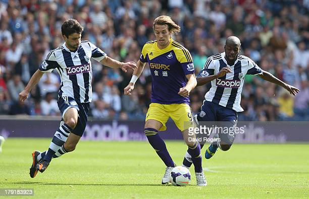 Miguel Michu of Swansea City is challenged by Claudio Yacob during the Barclays Premier League match between West Bromwich Albion and Swansea City at...