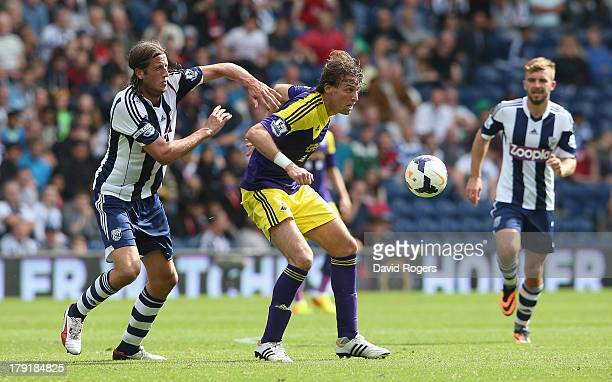 Miguel Michu of Swansea City is challenged by Jonas Olsson during the Barclays Premier League match between West Bromwich Albion and Swansea City at...