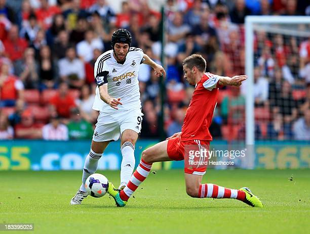 Miguel Michu of Swansea City is tackled by Morgan Schneiderlin of Southampton during the Barclays Premier League match between Southampton and...