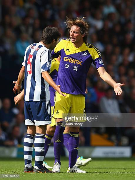 Miguel Michu of Swansea clashes with Claudio Yacob of West Brom during the Barclays Premier League match between West Bromwich Albion and Swansea...