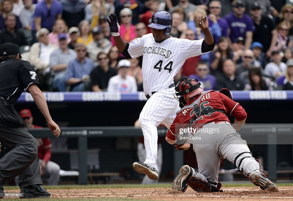 Miguel Montero (26) of the Arizona Diamondbacks can't make the tag on Juan Nicasio (44) of the Colorado Rockies as he scores on a base hit by Jordan Pacheco in the third inning April 21, 2013 at Coors Field.