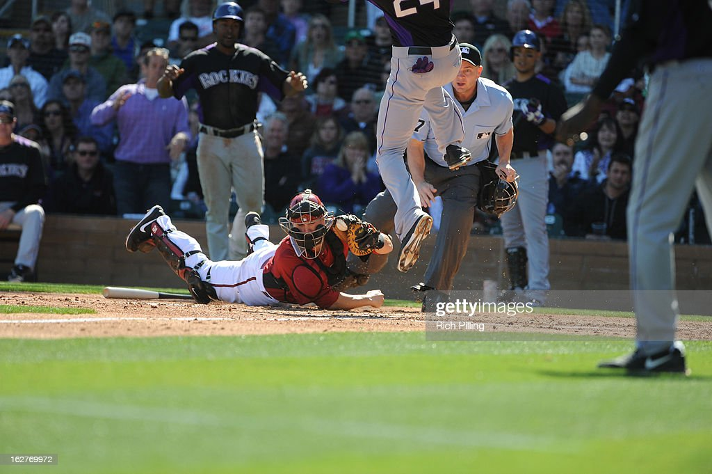 Miguel Montero #26 of the Arizona Diamondbacks lies on the ground after missing a tag on Dexter Fowler #24 of the Colorado Rockies during the spring training game on February 23, 2013 at the Salt River Fields at Talking Stick in Scottsdale, Arizona. The Rockies defeated the Diamondbacks 11-2.