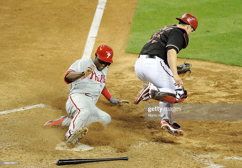Miguel Montero #26 of the Arizona Diamondbacks makes the force out at home plate and jumps out of the way of a sliding John Mayberry #15 of the Philadelphia Phillies at Chase Field on May 11, 2013 in Phoenix, Arizona.