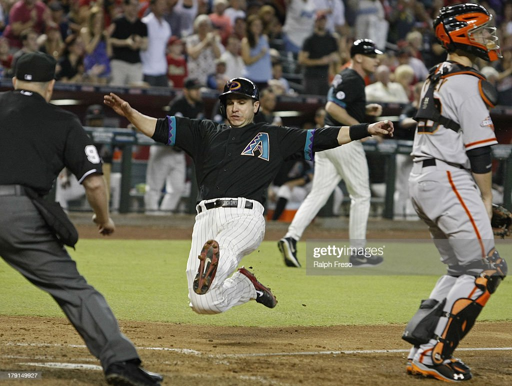 <a gi-track='captionPersonalityLinkClicked' href=/galleries/search?phrase=Miguel+Montero&family=editorial&specificpeople=836495 ng-click='$event.stopPropagation()'>Miguel Montero</a> #26 of the Arizona Diamondbacks slides past catcher <a gi-track='captionPersonalityLinkClicked' href=/galleries/search?phrase=Buster+Posey&family=editorial&specificpeople=4896435 ng-click='$event.stopPropagation()'>Buster Posey</a> #28 of the San Francisco Giants as he scores on the RBI single by teammate Willie Bloomquist #18 during the fourth inning of a MLB game at Chase Field on August 31, 2013 in Phoenix, Arizona.