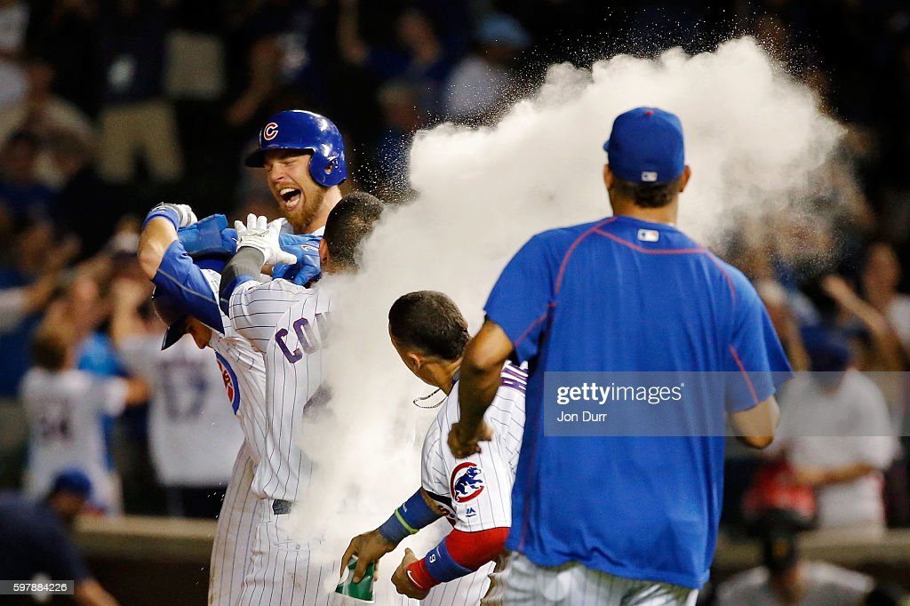 Miguel Montero of the Chicago Cubs celebrates with Ben Zobrist and Willson Contreras after hitting a walkoff RBI single against the Pittsburgh...