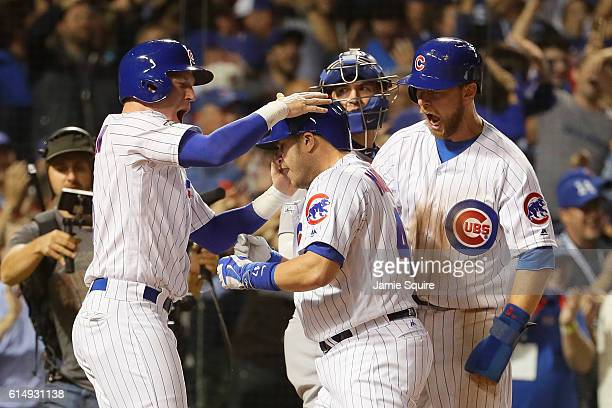 Miguel Montero of the Chicago Cubs celebrates with Chris Coghlan and Ben Zobrist after hitting a grand slam home run in the eighth inning against the...