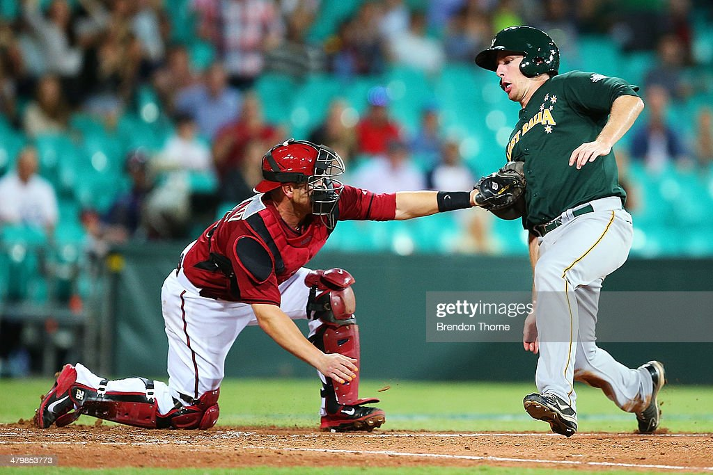 Miguel Montero of the Diamondbacks tags Mitch Dening of Australia on home plate during the match between Team Australia and the Arizona Diamondbacks...