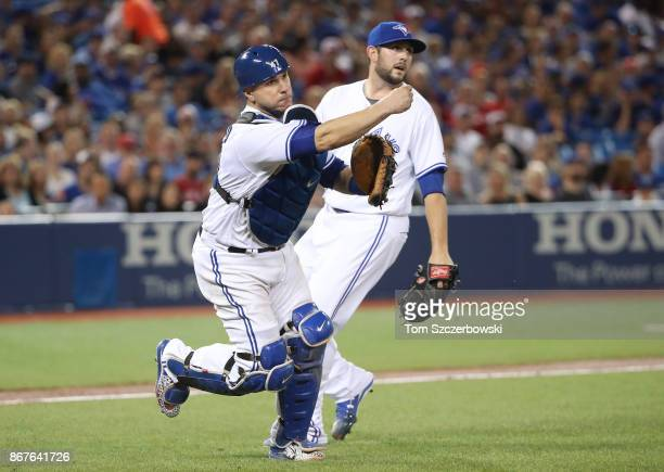 Miguel Montero of the Toronto Blue Jays fields a soft grounder and throws out Rajai Davis of the Oakland Athletics in the seventh inning during MLB...