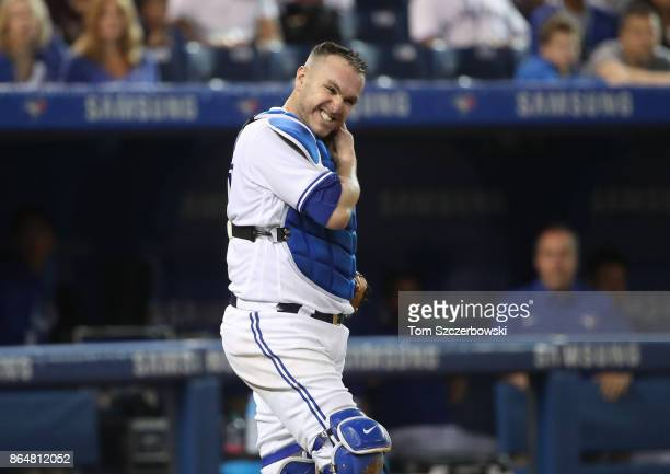 Miguel Montero of the Toronto Blue Jays grimaces as he reacts after being hit on the backswing by Steven Souza Jr #20 in the fifth inning during MLB...