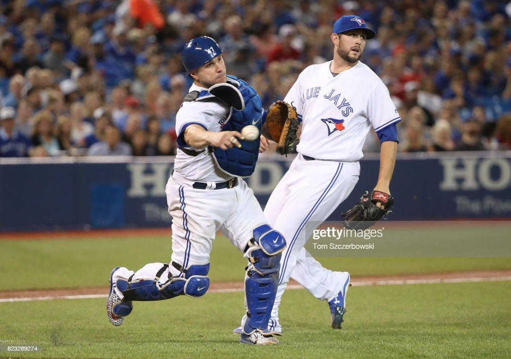 Miguel Montero #47 of the Toronto Blue Jays throws out Rajai Davis #11 of the Oakland Athletics in the seventh inning as Dominic Leone #51 watches during MLB game action at Rogers Centre on July 26, 2017 in Toronto, Canada.