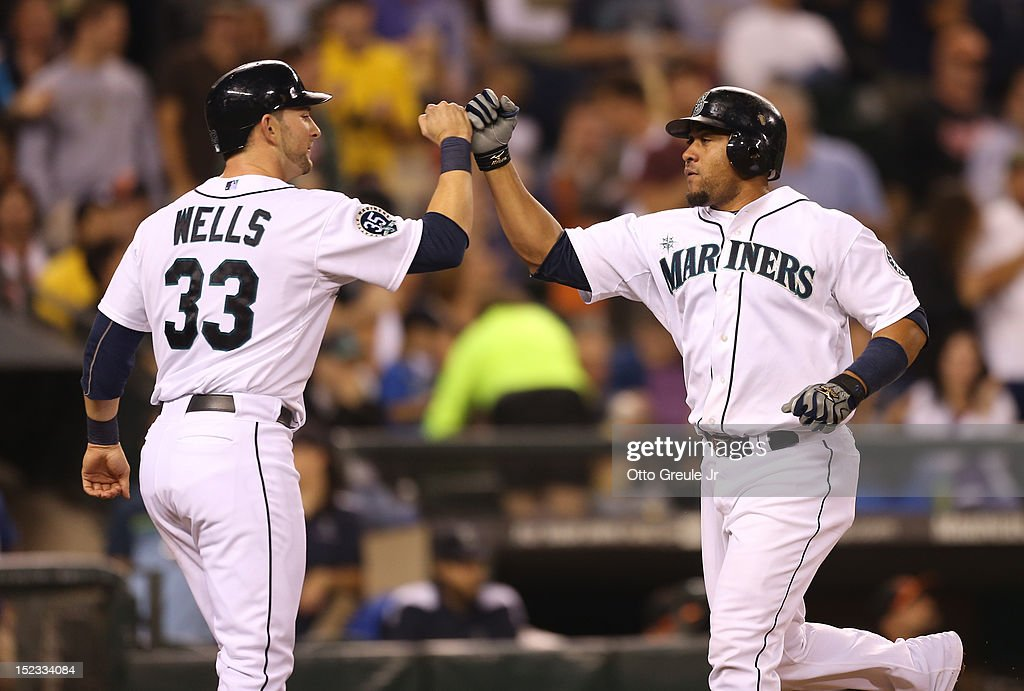 <a gi-track='captionPersonalityLinkClicked' href=/galleries/search?phrase=Miguel+Olivo&family=editorial&specificpeople=209185 ng-click='$event.stopPropagation()'>Miguel Olivo</a> #30 of the Seattle Mariners is congratulated by <a gi-track='captionPersonalityLinkClicked' href=/galleries/search?phrase=Casper+Wells&family=editorial&specificpeople=5747458 ng-click='$event.stopPropagation()'>Casper Wells</a> #33 after hitting a two-run homer against the Baltimore Orioles at Safeco Field on September 18, 2012 in Seattle, Washington.