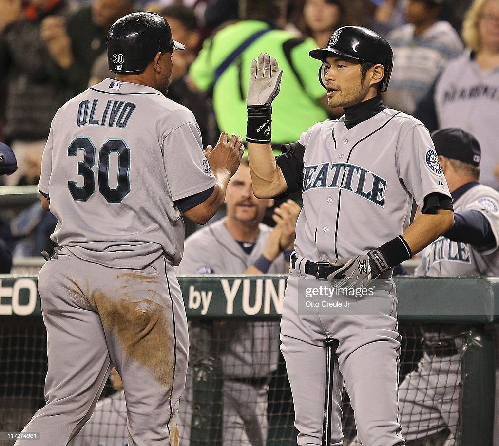 Miguel Olivo #30 of the Seattle Mariners is congratulated by Ichiro Suzuki #51 after scoring in the seventh inning against the Florida Marlins at Safeco Field on June 24, 2011 in Seattle, Washington. The Mariners defeated the Marlins 5-1.