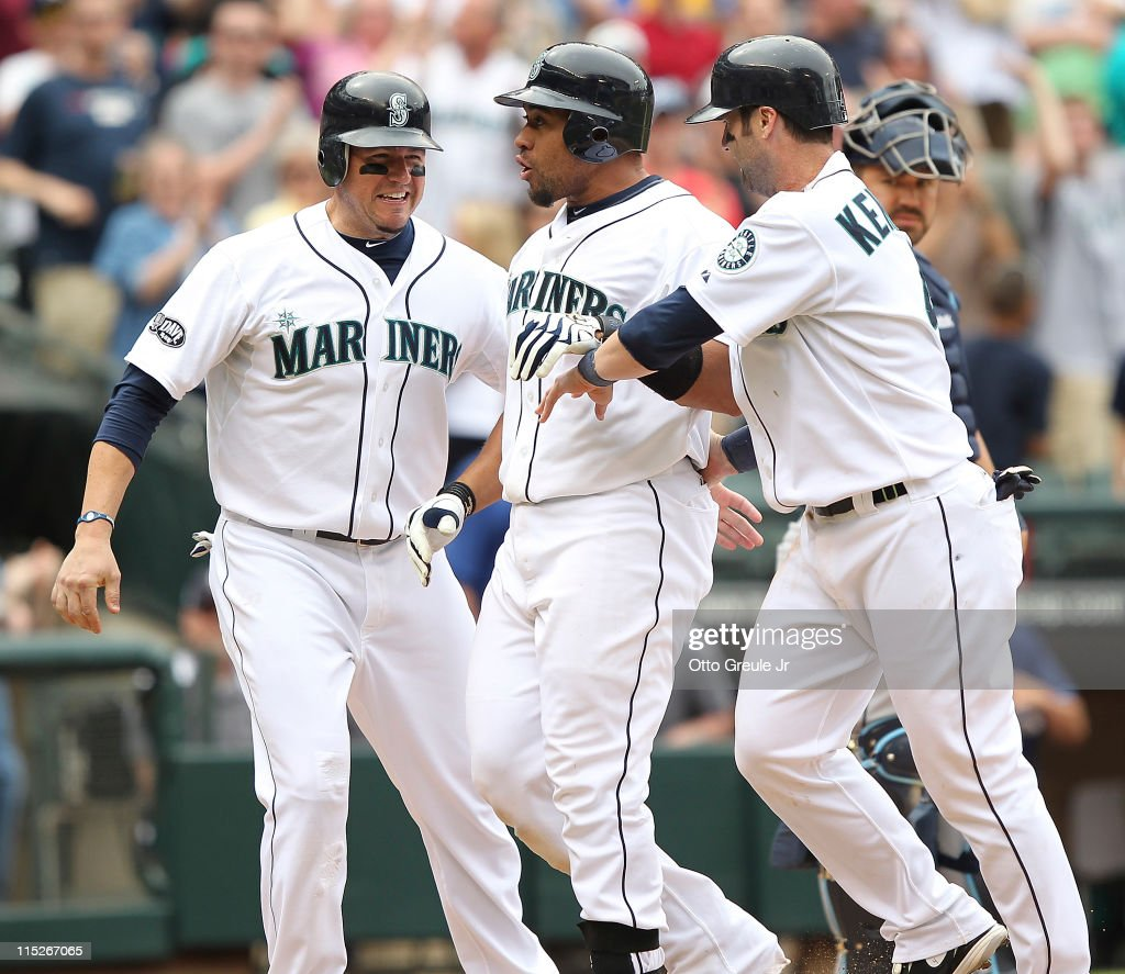 <a gi-track='captionPersonalityLinkClicked' href=/galleries/search?phrase=Miguel+Olivo&family=editorial&specificpeople=209185 ng-click='$event.stopPropagation()'>Miguel Olivo</a> #30 (M) of the Seattle Mariners is congratulated by <a gi-track='captionPersonalityLinkClicked' href=/galleries/search?phrase=Jack+Cust&family=editorial&specificpeople=730641 ng-click='$event.stopPropagation()'>Jack Cust</a> #29 (L) and <a gi-track='captionPersonalityLinkClicked' href=/galleries/search?phrase=Adam+Kennedy&family=editorial&specificpeople=184549 ng-click='$event.stopPropagation()'>Adam Kennedy</a> #4 after hitting a three run homer in the eighth inning to take a 9-6 lead against the Tampa Bay Rays at Safeco Field on June 5, 2011 in Seattle, Washington.