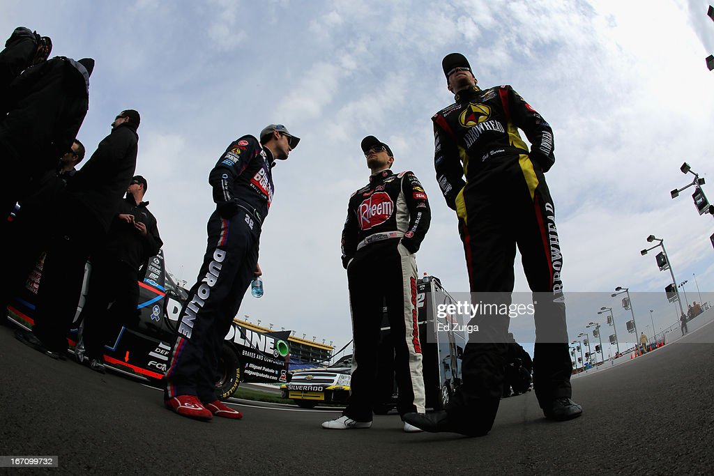 Miguel Paludo, driver of the #32 Duroline Chevrolet, James Buescher, driver of the #31 Rheem Chevrolet, and Jeb Burton, driver of the #4 Arrowhead Chevrolet, stand on the grid during qualifying for the NASCAR Camping World Truck Series SFP 250 at Kansas Speedway on April 20, 2013 in Kansas City, Kansas.