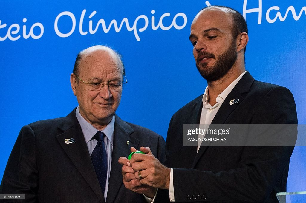 Miguel Roca Mas (L), First Vice President of the International Handball Federation (IHF), and former Brazilian handball player Bruno Souza during the draw of the handball tournaments of the Rio 2016 Olympic Games at Future Arena of Olympic Park in Rio de Janeiro, Brazil, on April 29, 2016. / AFP / YASUYOSHI