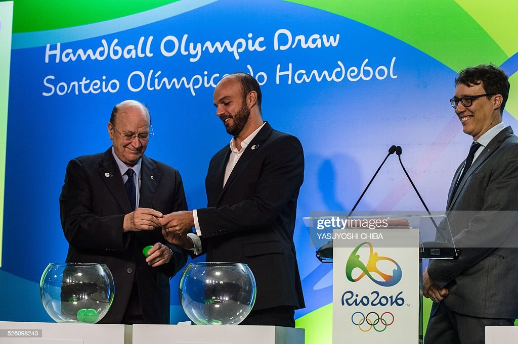 Miguel Roca Mas (L), First Vice President of the International Handball Federation (IHF), and former Brazilian handball player Bruno Souza (C) during the draw of the handball tournaments of the Rio 2016 Olympic Games at Future Arena of Olympic Park in Rio de Janeiro, Brazil, on April 29, 2016. / AFP / YASUYOSHI