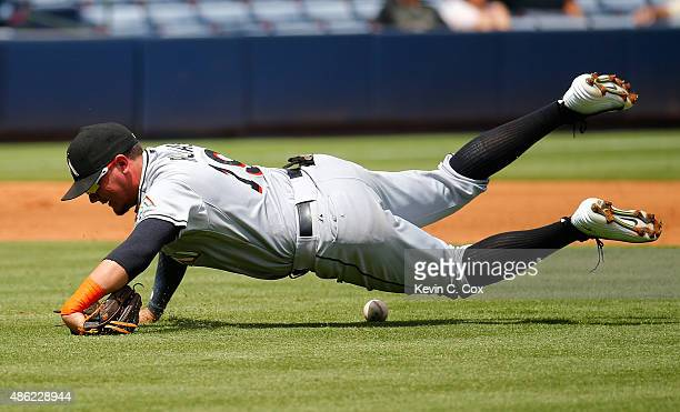 Miguel Rojas of the Miami Marlins falls to the ground as he fails to scoop up a single by Cameron Maybin of the Atlanta Braves in the third inning at...