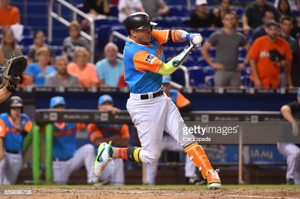 Miguel Rojas of the Miami Marlins hits the game winning sacrifice fly in the 11th inning against the San Diego Padres at Marlins Park on August 26...