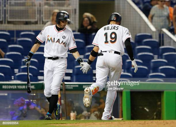 Miguel Rojas of the Miami Marlins is congratulated by teammate Ichiro Suzuki after Rojas' home run against the New York Mets at Marlins Park on...