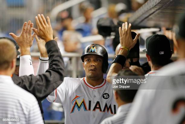 Miguel Rojas of the Miami Marlins is congratulated by teammates after he scored on a fifth inning single by Dee Gordon against the New York Mets at...