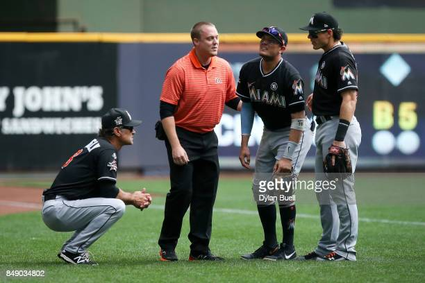 Miguel Rojas of the Miami Marlins is examined after being injured in the second inning against the Milwaukee Brewers at Miller Park on September 17...