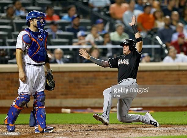 Miguel Rojas of the Miami Marlins scores in the ninth inning as Travis d'Arnaud of the New York Mets stands by on September 16 2015 at Citi Field in...
