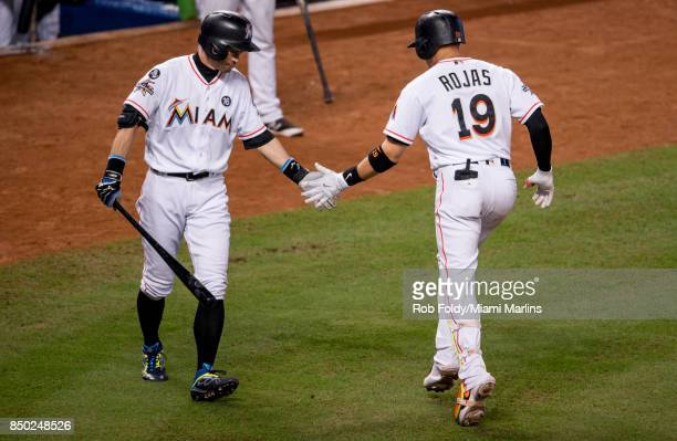 Miguel Rojas of the Miami Marlins shakes hands with Ichiro Suzuki after hitting a home run during the eighth inning against the New York Mets at...